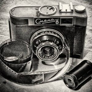 Zdjęcie czarno-białe. Wygląda jak grafika. Przedstawia analogowy aparat fotograficzny, z przodu po lewej stronie znajduje się klisza.