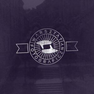 Grafika promocyjna, w kształcie kwadratu. Na ciemnym, granatowym tle białe okrągłe logo z napisem Warsztat fotograficzny.