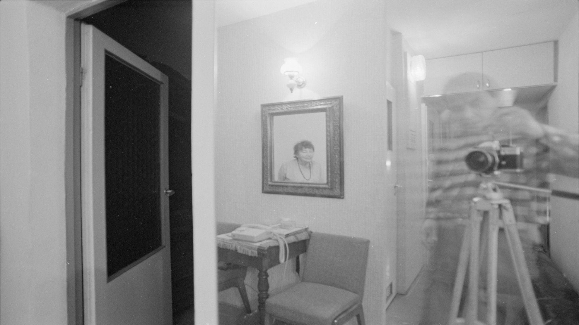 czarno-białe zdjęcie przedstawiające wnętrze domu. widoczny zarys osoby stojącej przy aparacie fotograficznym na statywie