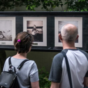 A man and a woman looking at photos from the exhibition