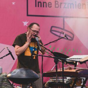 mężczyzna stoi przy mikrofonie. wokół niego znajdują się różne nietypowe instrumenty muzyczne