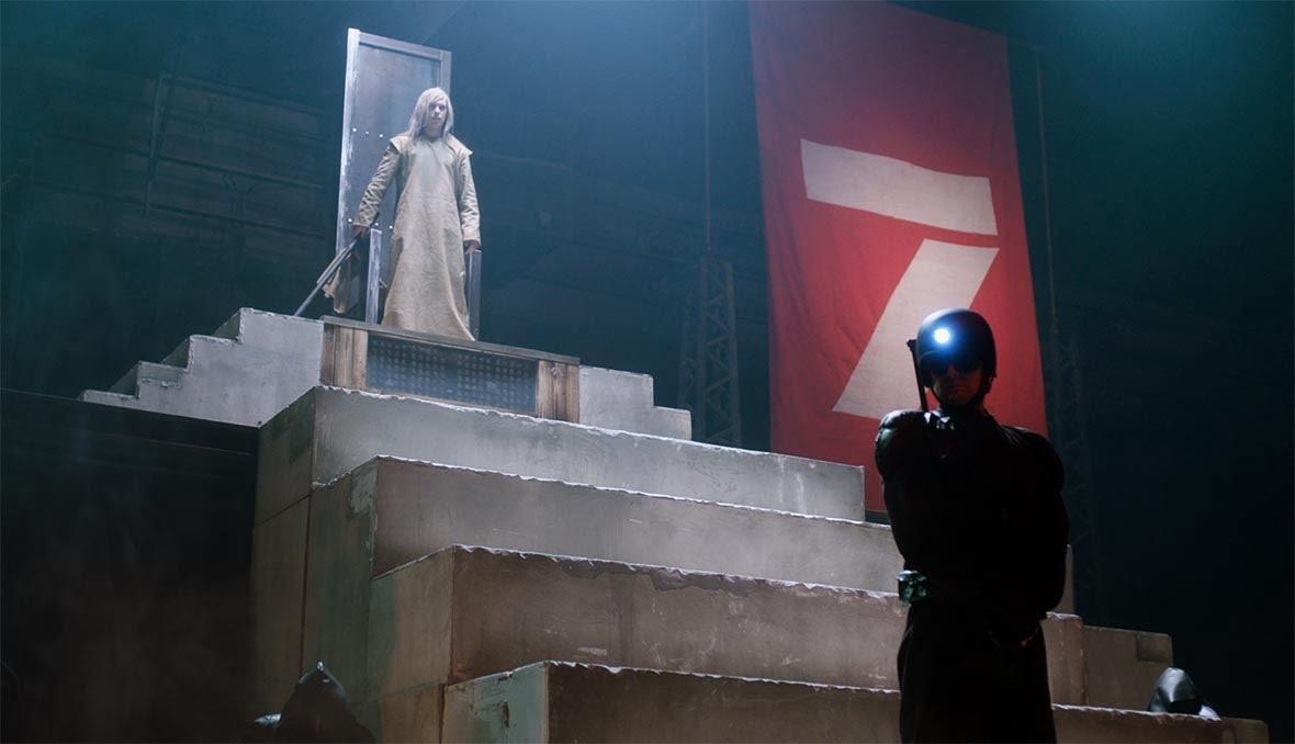 Kadr z filmu. na szczycie betonowych schodów metalowy tron z którego wstała długowłosa postać. u dołu schodów ubrany w ciemną odzież mężczyzna. na jego głowie kask i latarka czołówka
