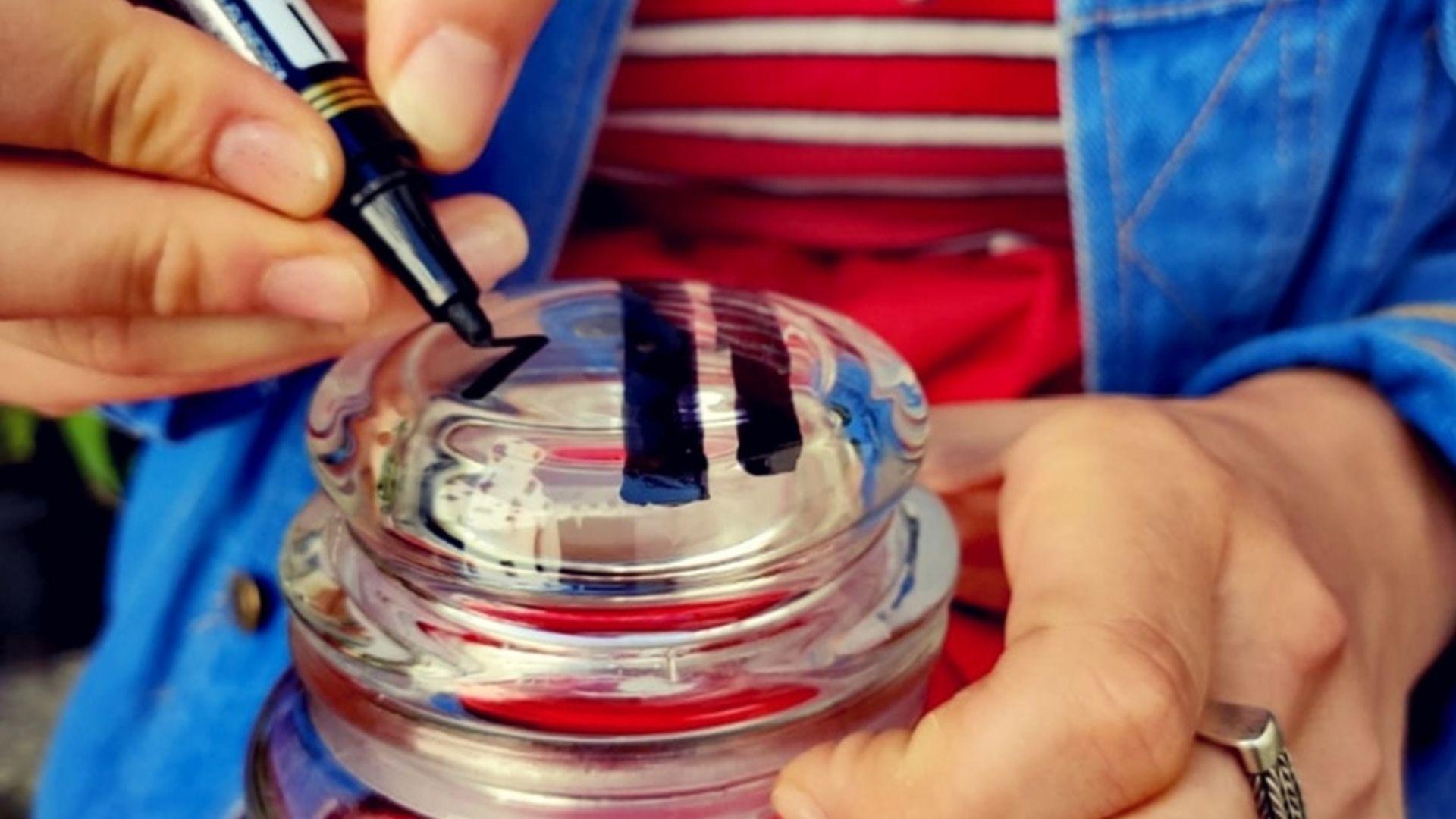 zdjęcie ilustracyjne. szklany słoik ze szklaną pokrywką, dłonie trzymające mazak typu marker malują wzorki na pokrywce