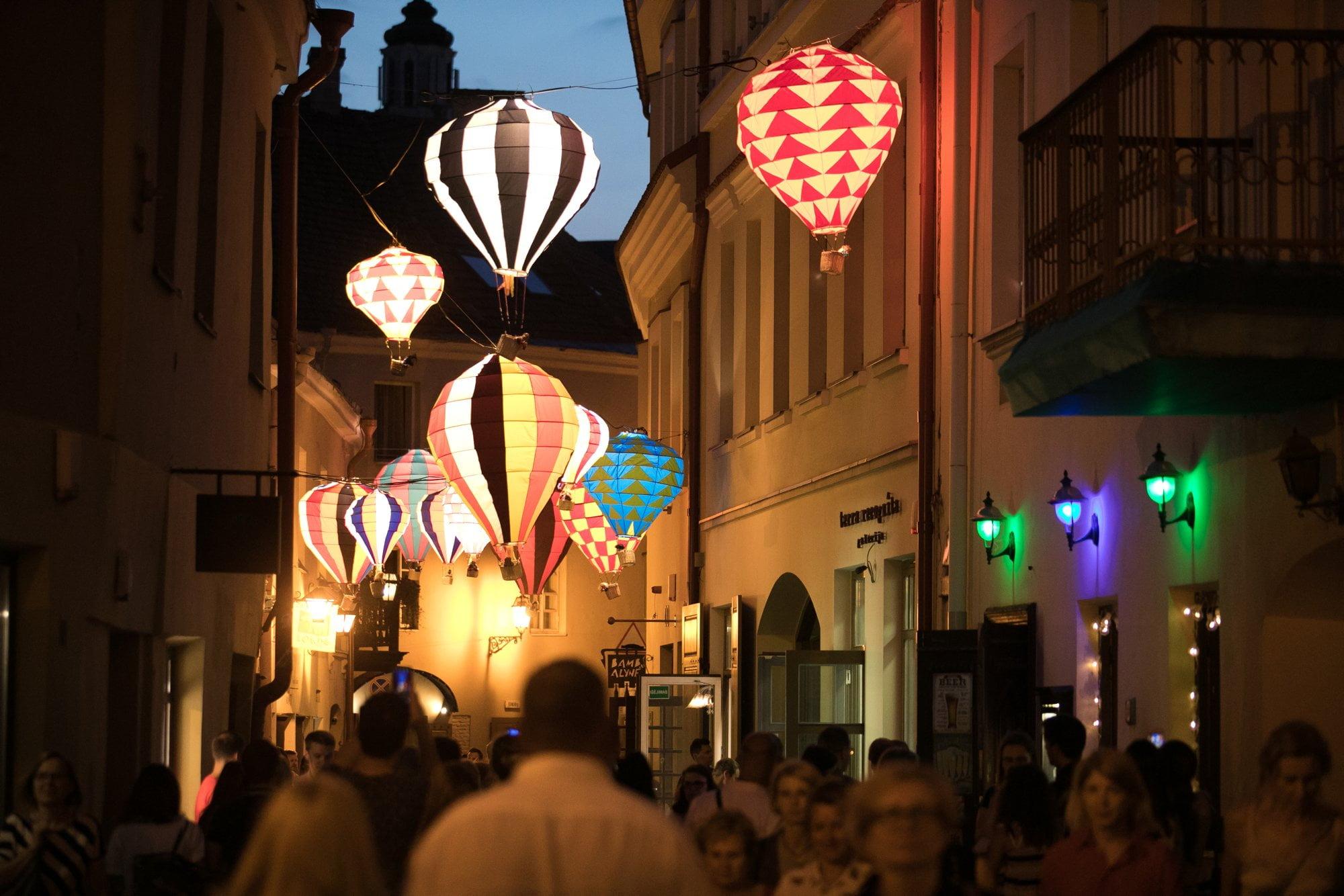 zdjęcie ilustracyjne. Tłum osób podczas Nocy Kultury, ponad głowami podświetlona instalacja artystyczna składająca się z małych kolorowych balonów lotniczych