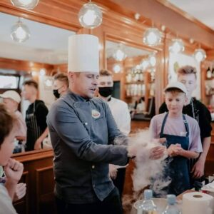 Zdjęcie ilustracyjne przedstawia Szefa Kuchni pokazującego efekt stosowania suchego lodu oraz grupę chłopców obserwujących z zainteresowaniem jego pracę