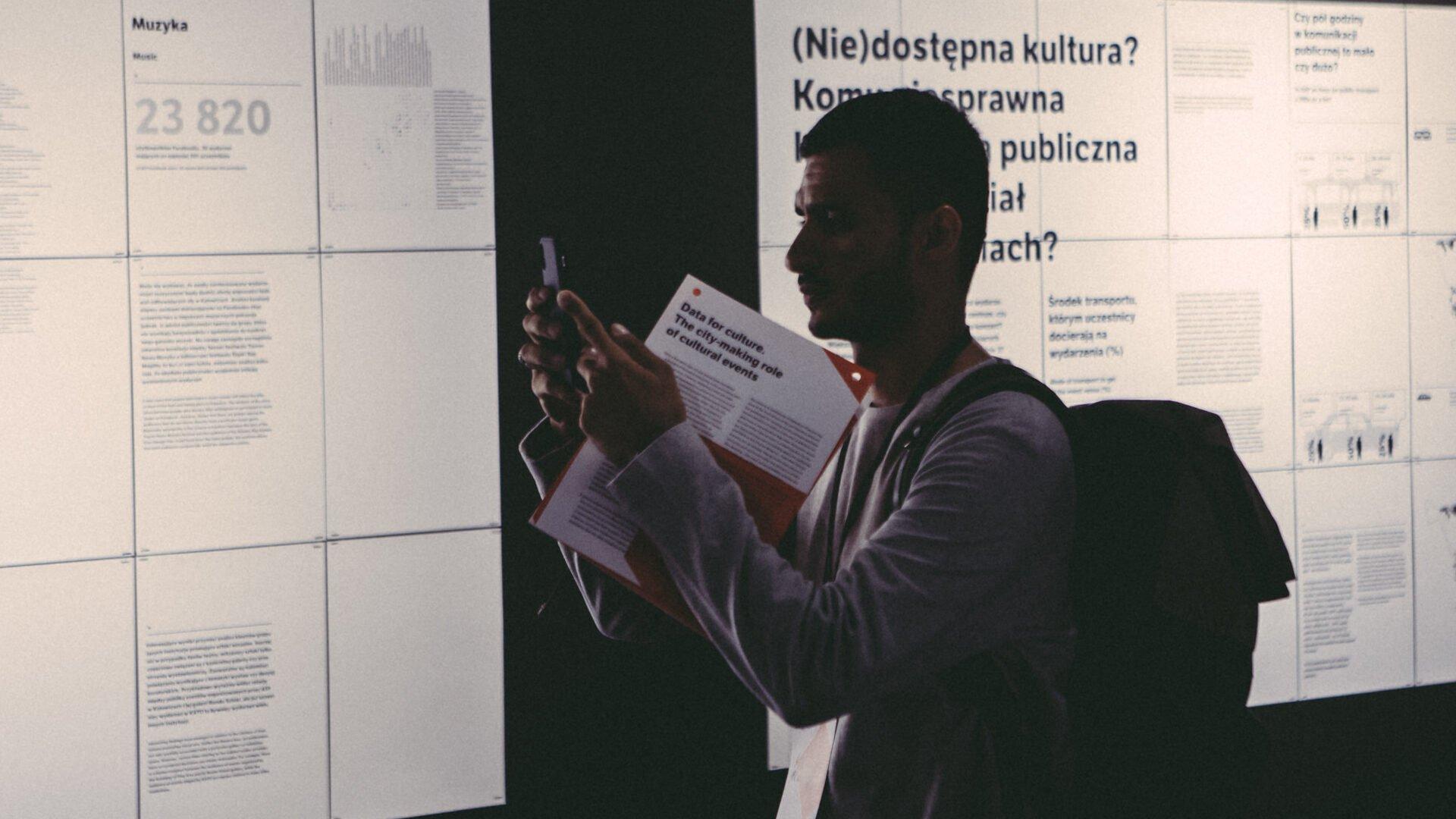 Zdjęcie pokazujące mężczyznę robiącego zdjęcie telefonem komórkowym. Znajduje się w instytucji kultury i ogląda ekspozycję. W ręku ma folder informacyjny.