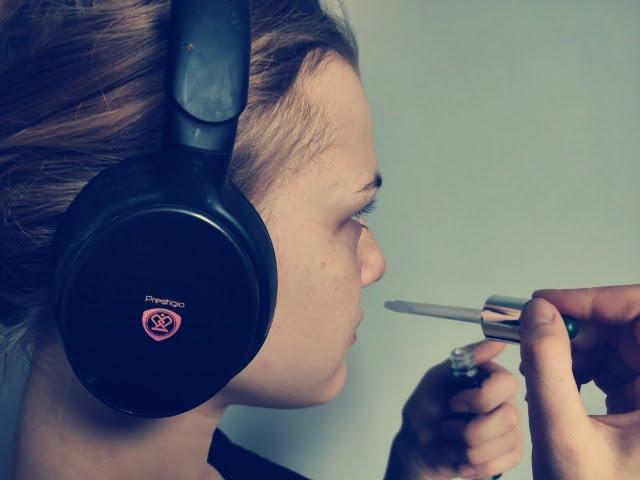 Zdjęcie ilustracyjne przedstawiające młodą dziewczynę w słuchawkach na uszach, która sprawdza zapach z buteleczki przykładając do nosa pipetę z zakraplaczem.