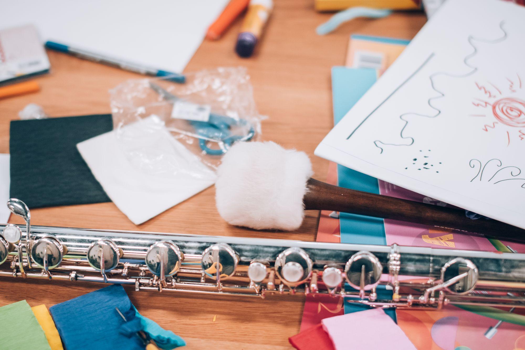 Zdjęcie ilustracyjne przedstawia stół, instrumenty muzyczne oraz przybory do pisania