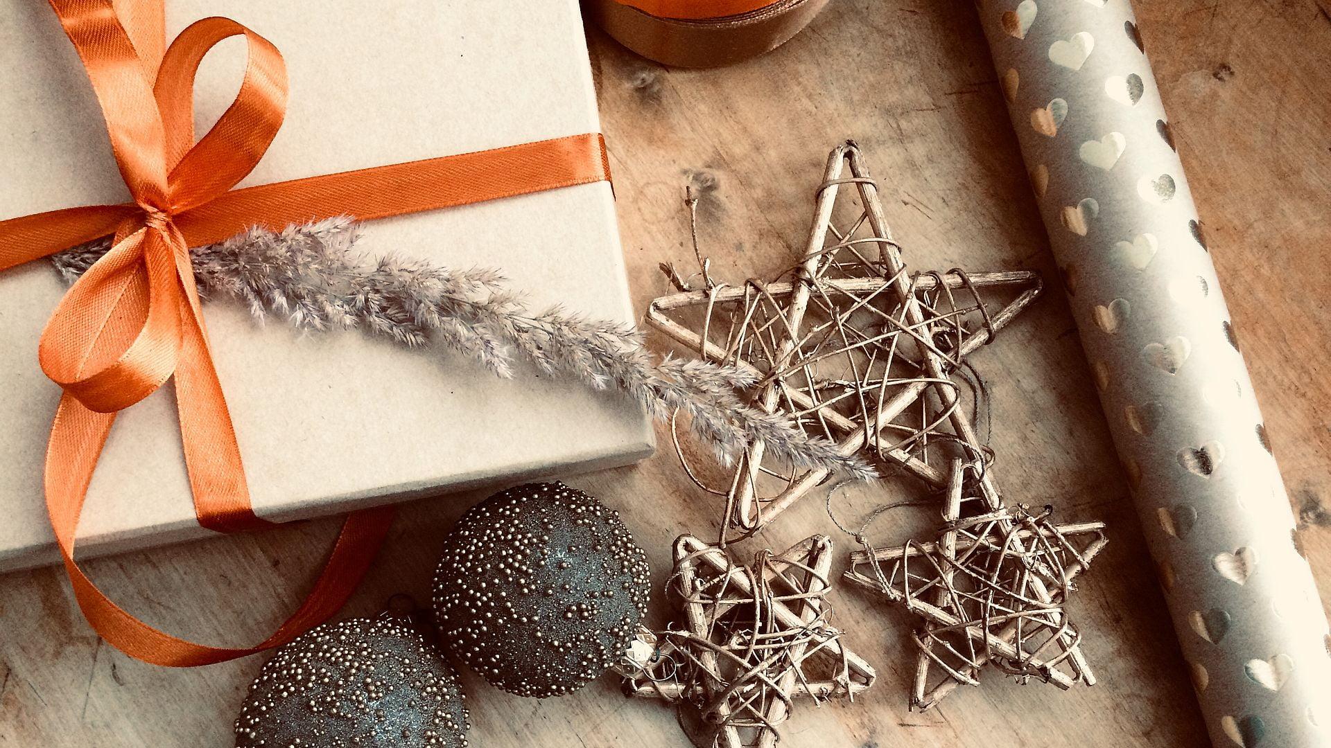 na drewnianym blacie leżą ozdoby choinkowe - dwie szklane bombki i 3 gwiazdki z gałązek, obok tekturowe pudełko z pomarańczową kokardką i rolka ozdobnego papieru. Wszystko w ciepłej, złocistej tonacji
