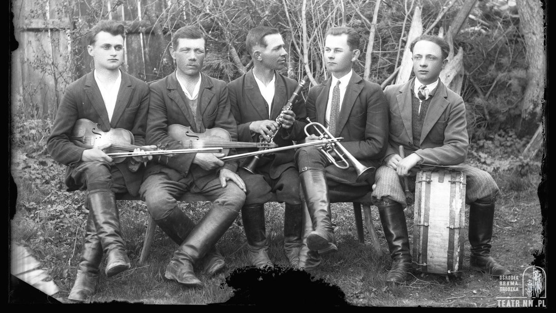 Dawna pozowana czarno-biała fotografia. Na dworze, na drewnianej ławeczce siedzi pięciu mężczyzn. Każdy z nich trzyma instrument. Są to dwie pary skrzypiec, klarnet, trąbka i bęben - baraban.