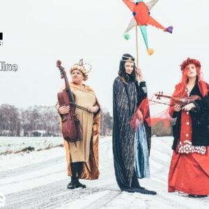 Trzy kobiety w egzotycznych, połyskujących strojach stoją na polnej drodze pokrytej śniegiem. Na głowach mają korony, a w rękach trzymają skrzypce, gwiazdę kolędniczą - atrybut kolędników i basy.. W tle domy i drzewa. W prawym górnym rogu logo Jarmarku Jagiellońskiego oraz hasztag kulturaonline. Autorką zdjęcia jest Marianna Łakoma, grafikę do promocji wydarzenia przygotowała Ilona Wałęcak