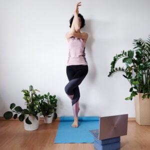 Na zdjęciu, w otoczeniu roślin doniczkowych, osoba w stroju gimnastycznym stoi na jednej nodze na niebieskiej macie, ma przed sobą laptopa. Unosi skrzyżowane ramiona zasłaniając twarz.