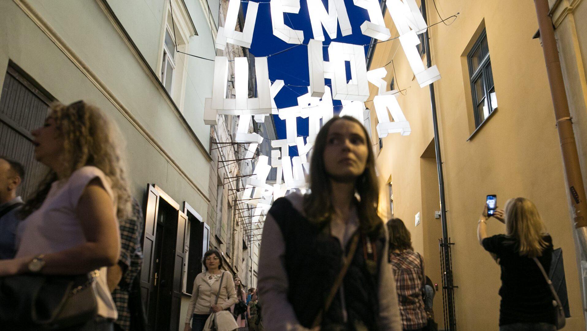 Zdjęcie wykonane podczas Nocy Kultury.Ludzie w wąskiej uliczce, nad ulicą zawieszone duże białe, święcące litery