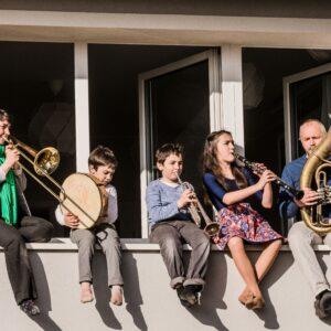 zdjęcia przedstawia grupę osób, w tym dwójkę dorosłych i trójkę dzieci, siedzących na parapecie na zewnątrz okna. Każdy ma w rękach inny instrument.