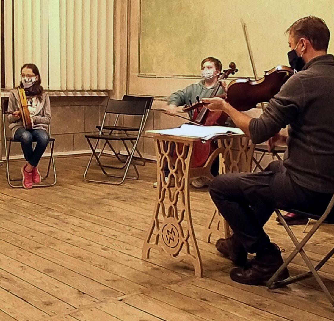 zdjęcie przedstawia obszerną salę, w której parę osób w maskach ćwiczy grę na różnych instrumentach. Siedzą w dużych odległościach od siebie, każda z osób gra na innym instrumencie.