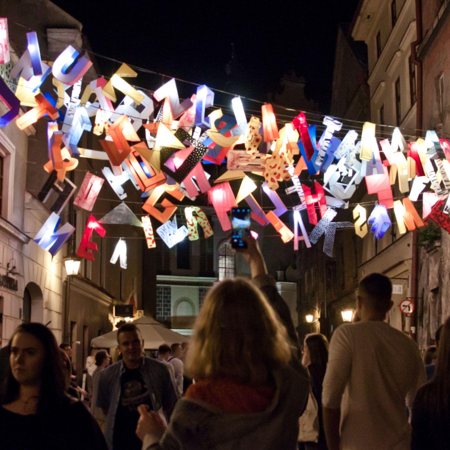 Zdjęcie wykonane podczas Nocy Kultury, noc, ulica Starego Miasta, w dole tłum, pomiędzy kamienicami na wysokości drugiego piętra rozciągnięta instalacja artystyczna. Liny na których powieszone są kolorowe litery - rozsypany alfabet, świecą się.