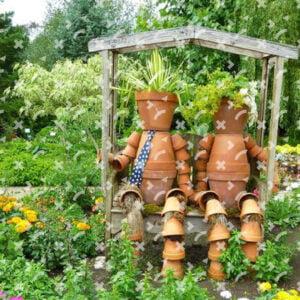 obrazek przedstawia piękny ogród pełen kwiatów. W centrum drewniana półka z daszkiem, na której umieszczone zostały doniczki, które swoim ustawieniem przypominają siedzące postacie.