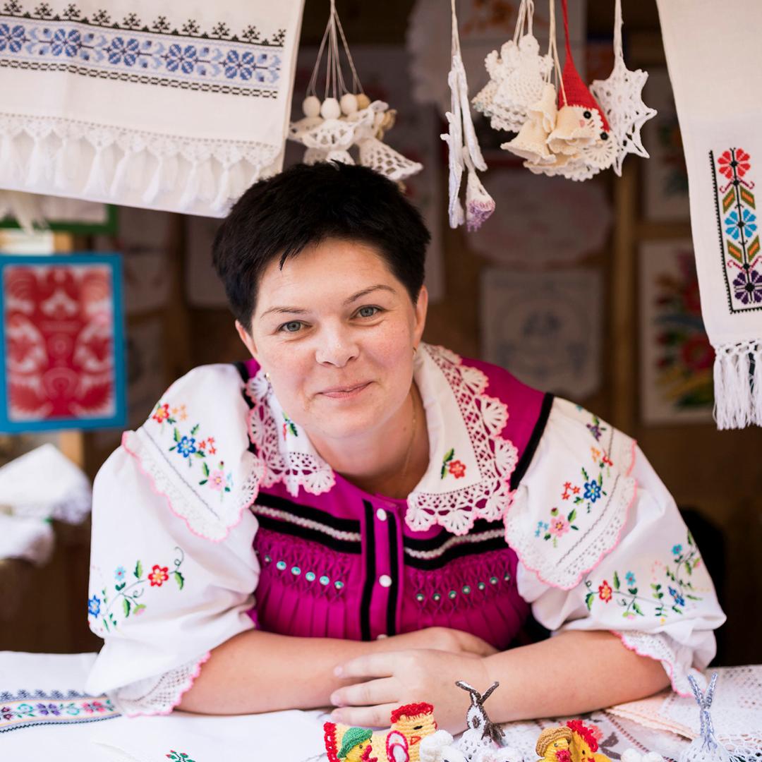 Zdjęcie przedstawia twórczynię ludową w ujęciu portretowym. Rękoma opiera się o blat stoiska, na którym wyeksponowane są wyroby tradycyjne.
