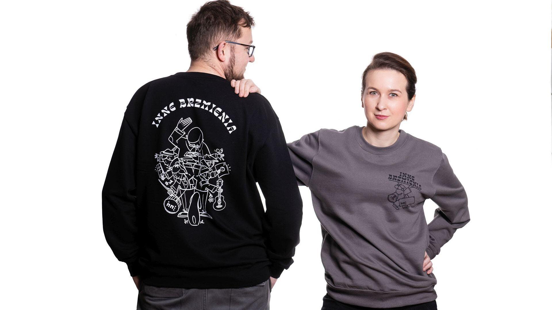dwie osoby, kobieta i mężczyzna stoją obok siebie. Kobieta przodem, mężczyzna tyłem. Obydwoje ubrani w takie same bluzy, w dwóch różnych kolorach, czarnym i szarym. z tyłu czarnej bluzy duży biały nadruk, z przodu szarej bluzy niewielki nadruk po lewej stronie