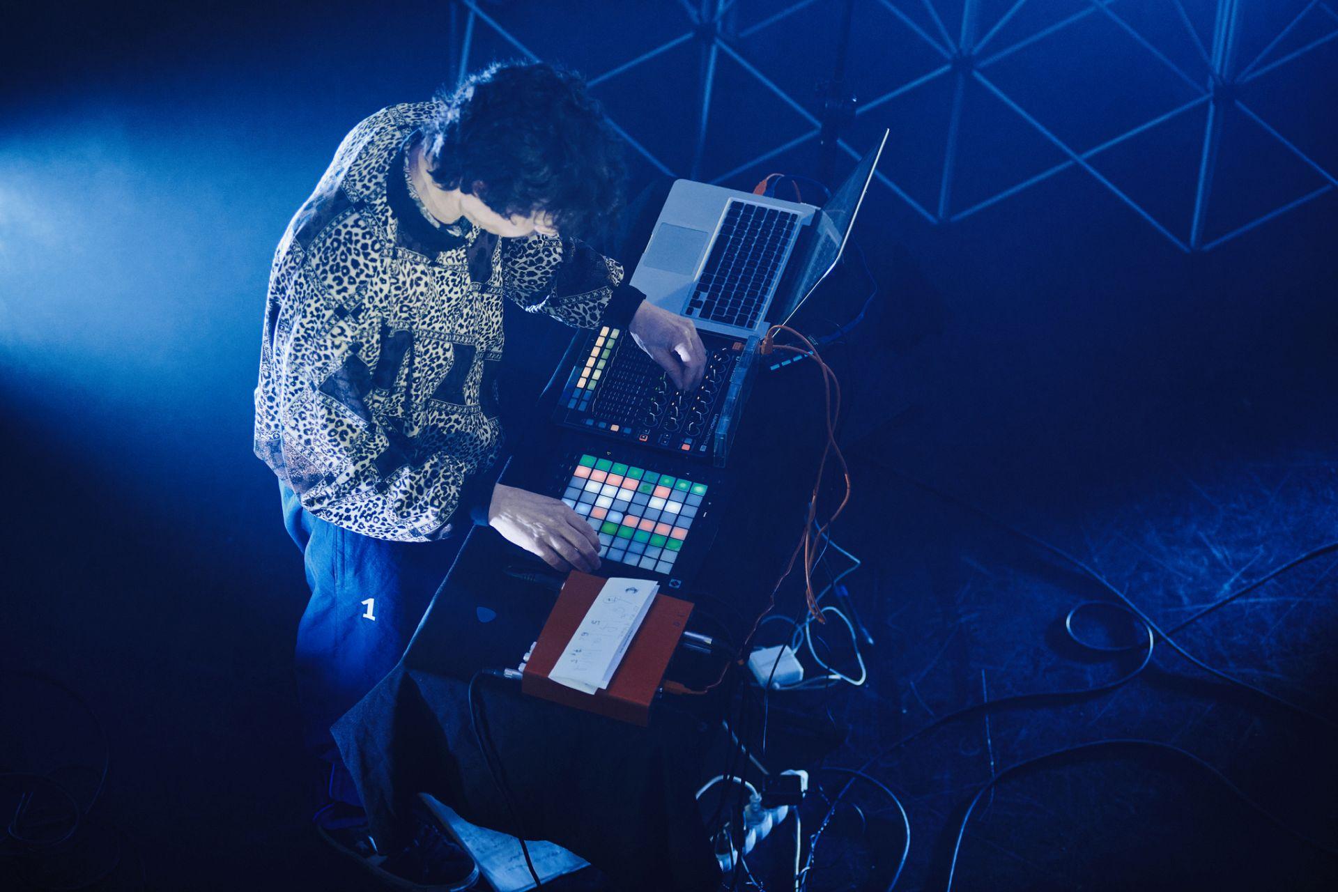 widok z góry na mężczyznę przy stole zastawiony sprzętem elektroniczym. kolorowe diody, komputer, dużo kabli