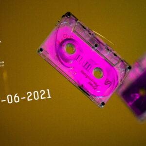 brudno miodowe tło na którym znajdują się dwie różowe kasety magnetofonowe