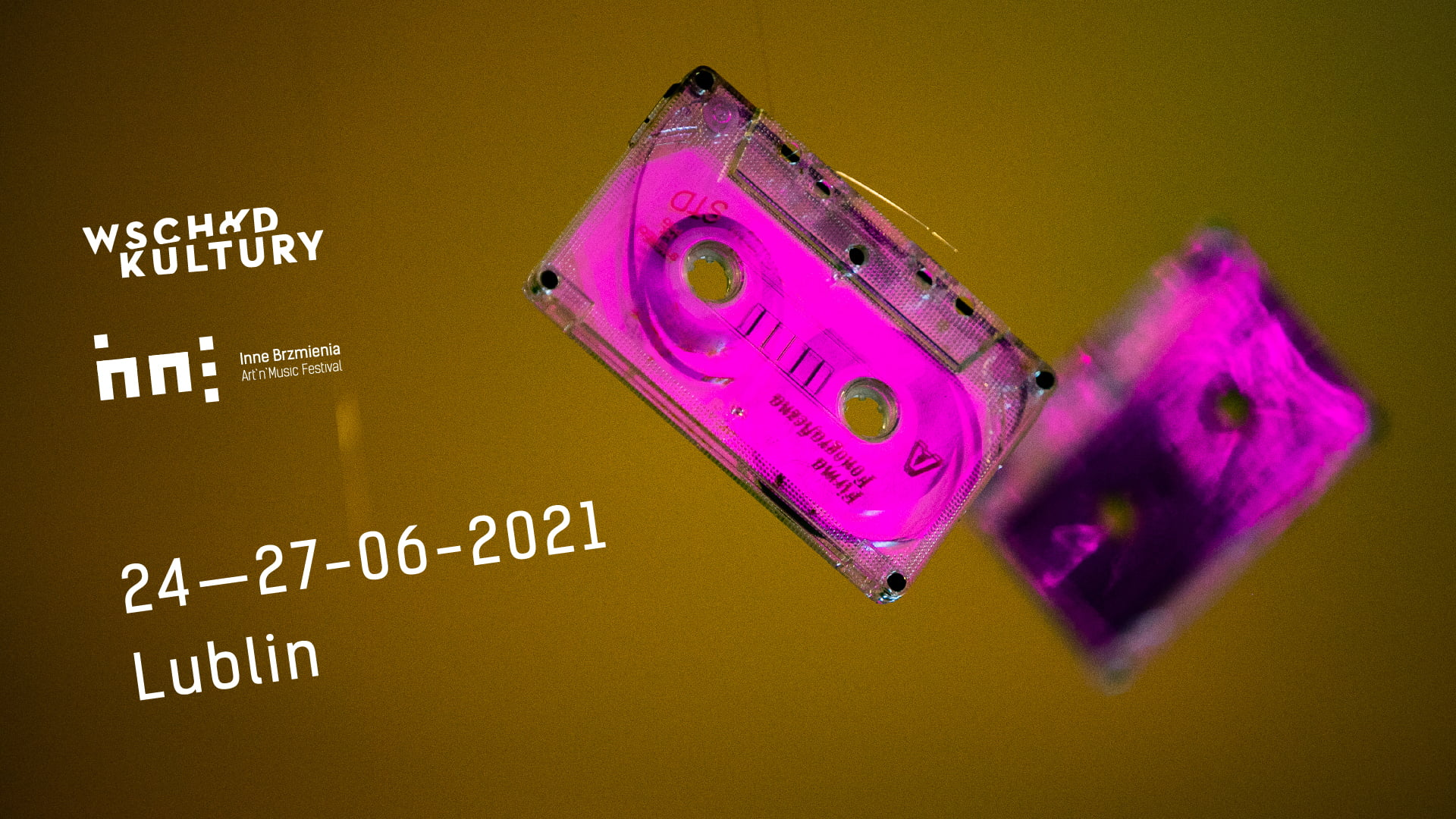 brudno miodowe tło na którym znajdują się dwie różowe kasety magnetofonowe, jedna nieostra. napisy: wschód kultury Inne brzmienia 24-27-06 2021 Lublin