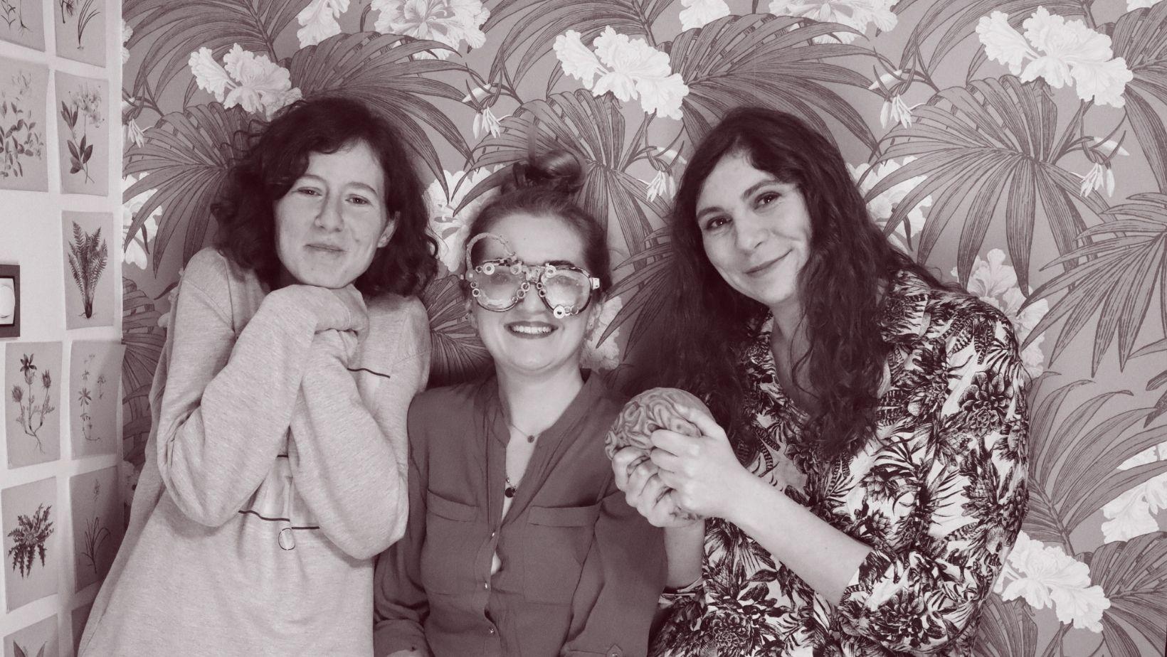 czarno białe zdjęcie, trzy młode uśmiechnięte kobiety na tle ściany w roślinne motywy.
