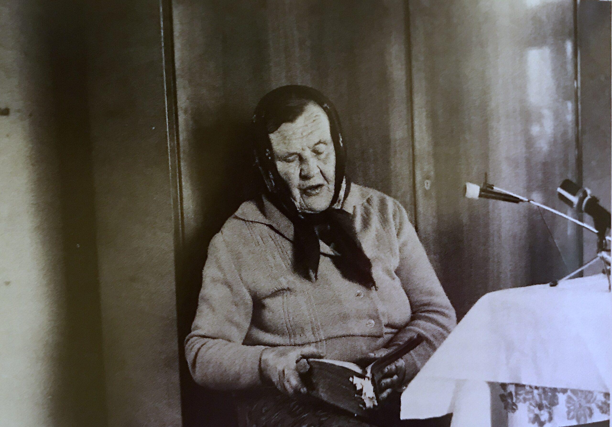 Fotografia archiwalna, widzimy siedzącą starszą kobietę, w chustce na głowie, która w rękach trzyma książeczkę/ zeszyt. Kobieta śpiewa spoglądając do książeczki/ zeszytu. Na stoliku koło kobiety stoją mikrofony.