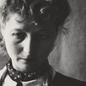 Czarno-białe zdjęcie kobiety z chustą w kropki na szyi.