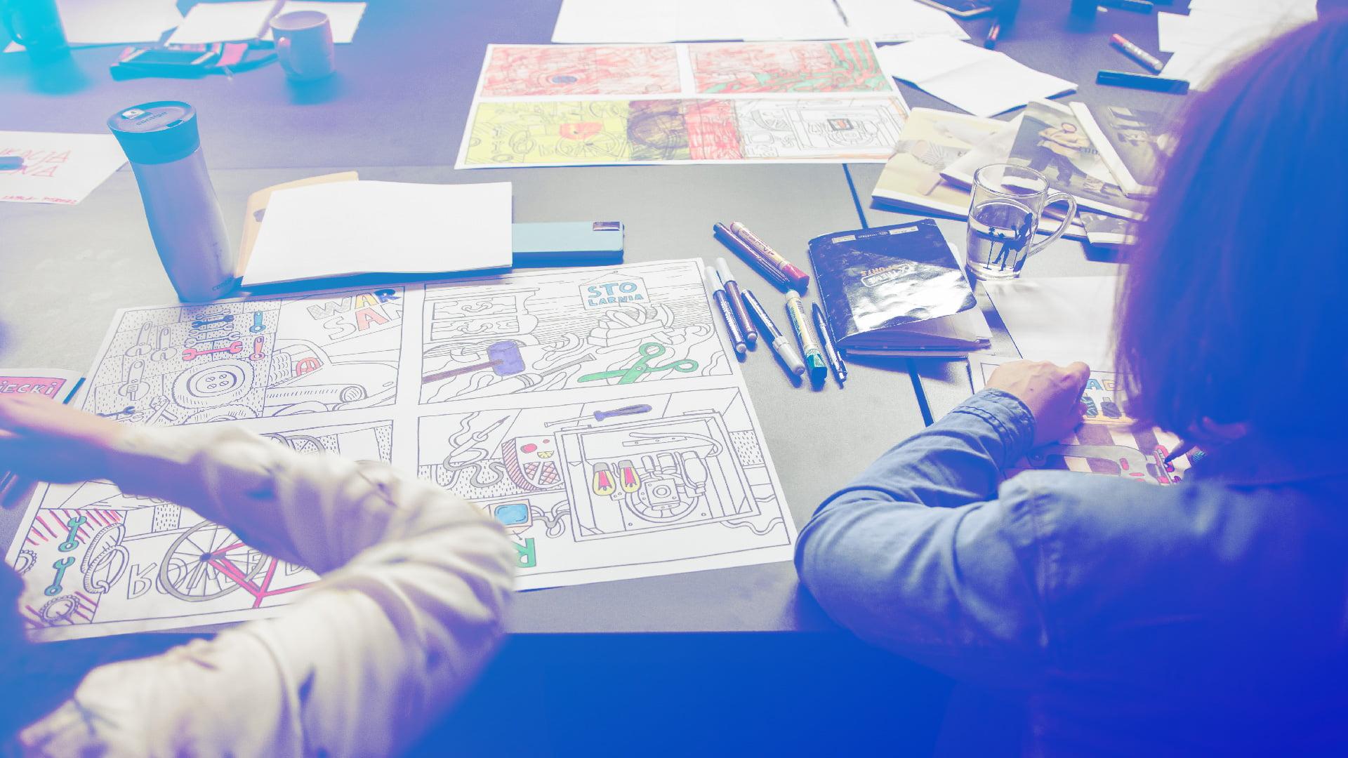Stół, na którym leżą markery, zeszyty, obrazki oraz kartki z rysunkami.