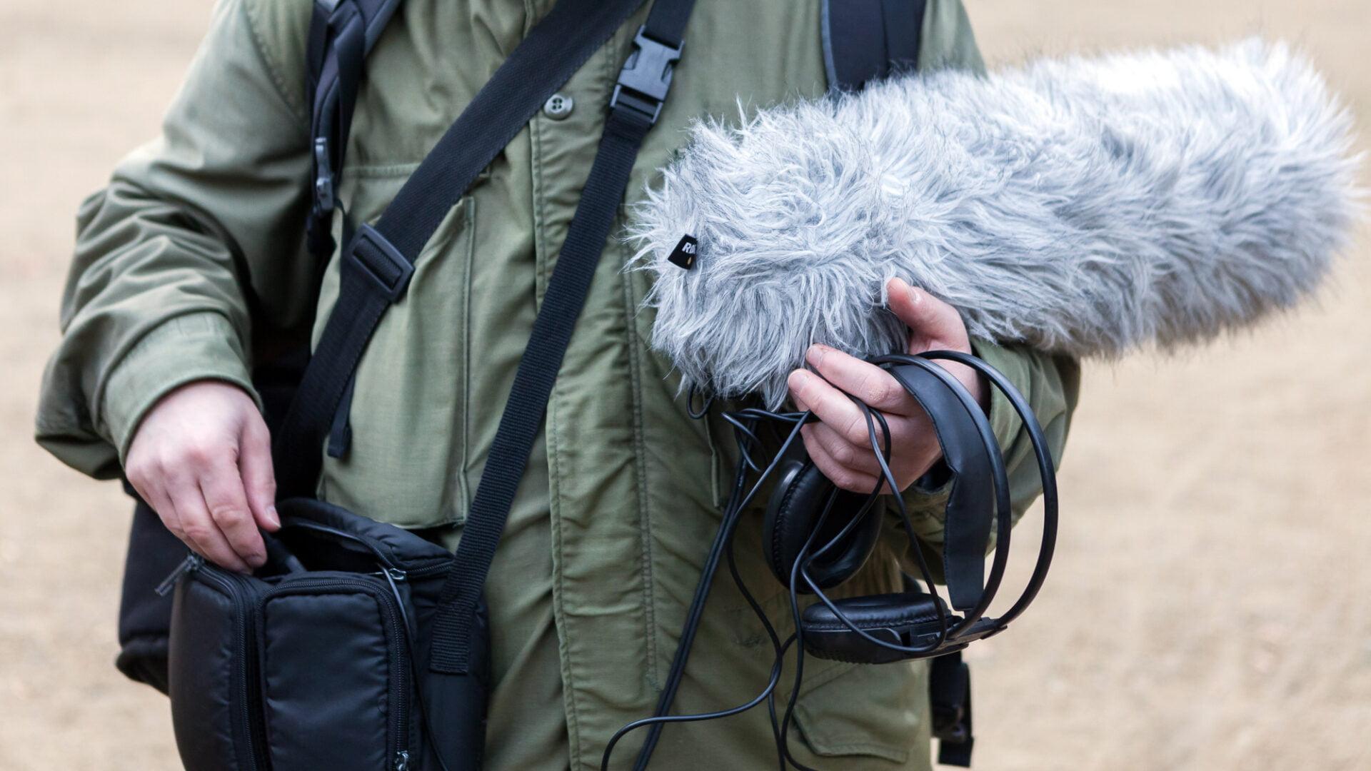 Osoba z zieloną kurtką ma czarną torbę oraz trzyma mikrofon i słuchawki.