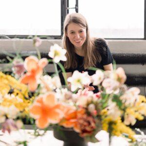 zdjęcie przedstawia uśmiechnięta kobietą z jasnymi, długim włosami, patrzy na kolorowy bukiet