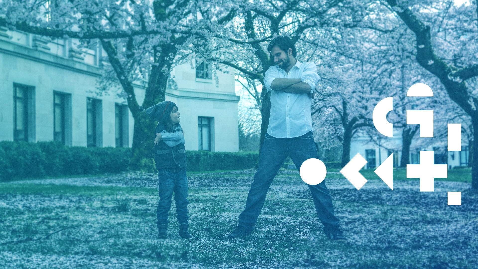 Mężczyzna oraz dziecko stojący w trawie, pośród kwitnących drzew. W prawej części grafiki znajdują się geometryczne elementy.