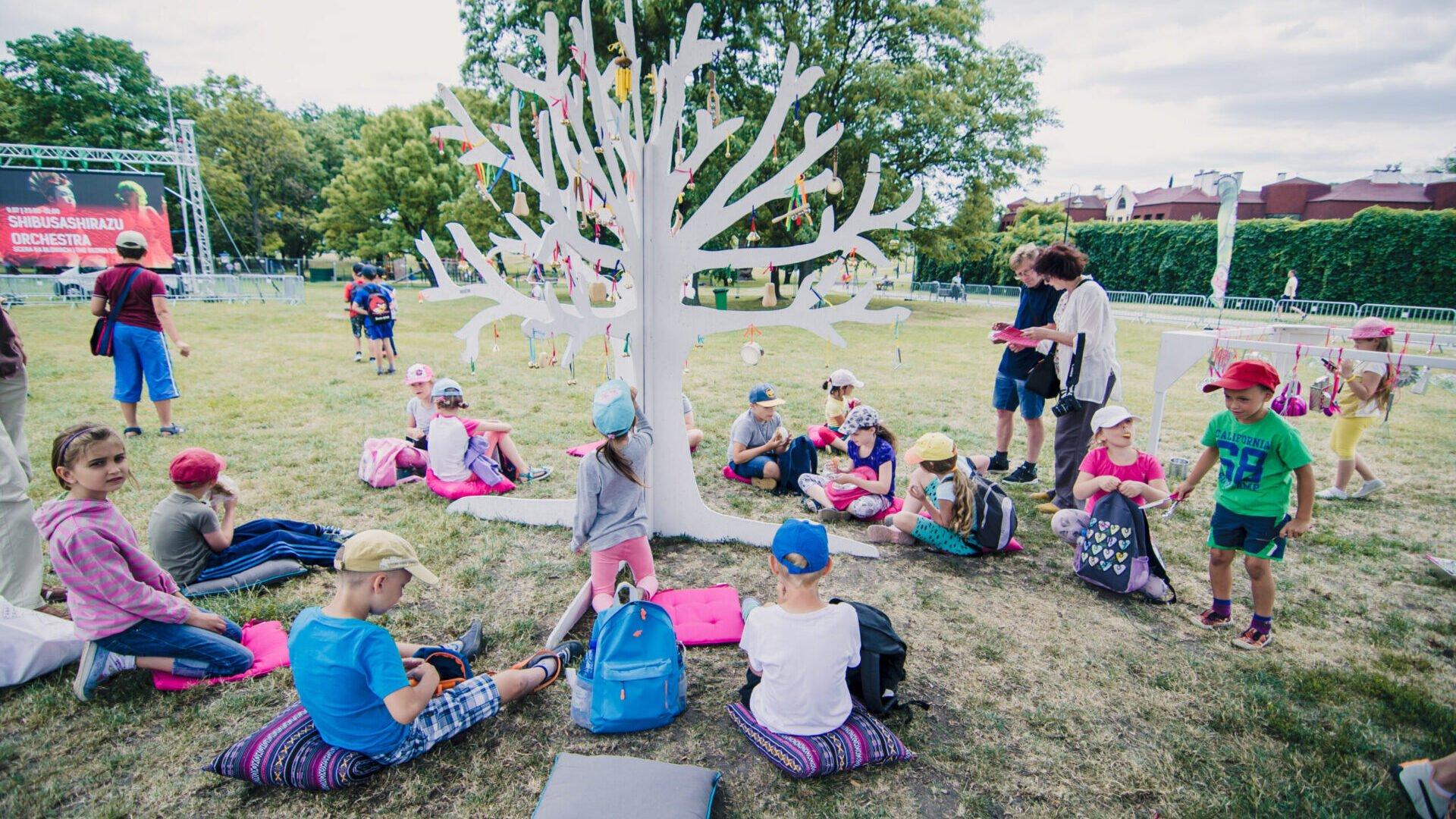 Grupa dzieci siedząca na poduszkach na trawie wokół białej makiety drzewa z instrumentami muzycznymi.