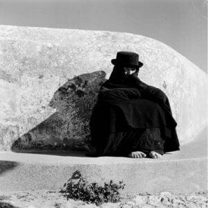 Kobieta w czarnym ubraniu oraz czarnym kapeluszu siedzi skulona i oparta o kamień. Zdjęcie czarno białe.