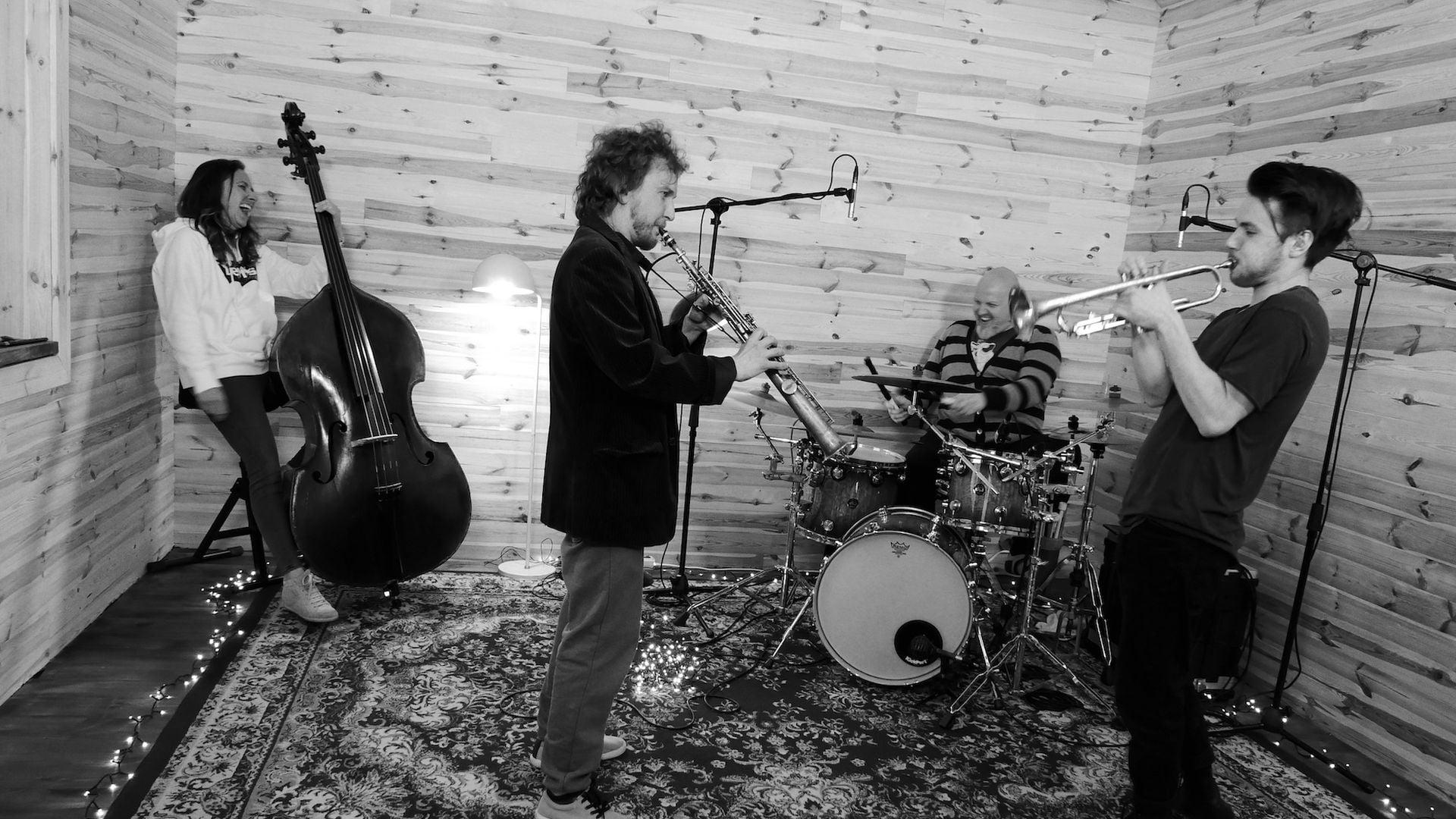 Na zdjęciu widzimy cztery osoby z instrumentami, trzech mężczyzn i jedną kobietę. Na drugim planie jest kobieta uśmiechnięta, siedzi na krześle i trzyma kontrabas oraz uśmiechnięty mężczyzna grający na perkusji . Na pierwszym planie mężczyzna grający na klarnecie. Naprzeciwko mężczyzna grający na trąbce. Zdjęcie zostało wykonane w zamkniętym pomieszczeniu.