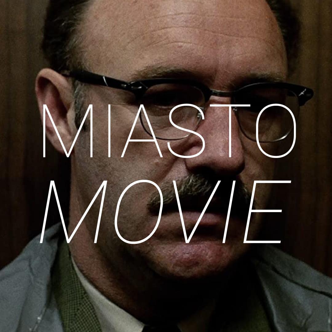 Zdjęcie twarzy mężczyzny w okularach oraz z wąsem. Napis Miasto Movie.