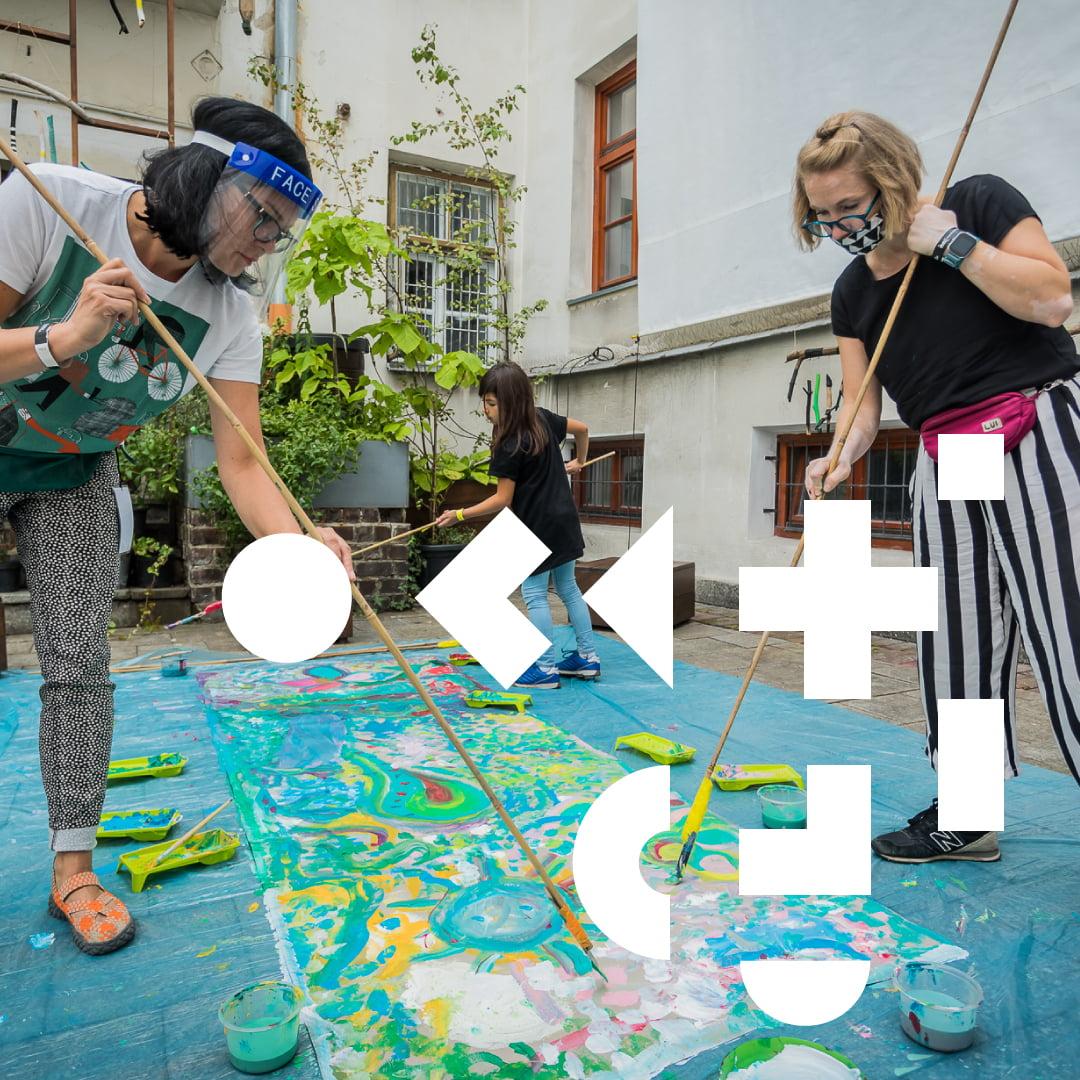 Trzy osoby malujące po materiale za pomocą pędzli na wysięgnikach. Na środku geometryczne elementy. W tle budynek oraz rośliny.