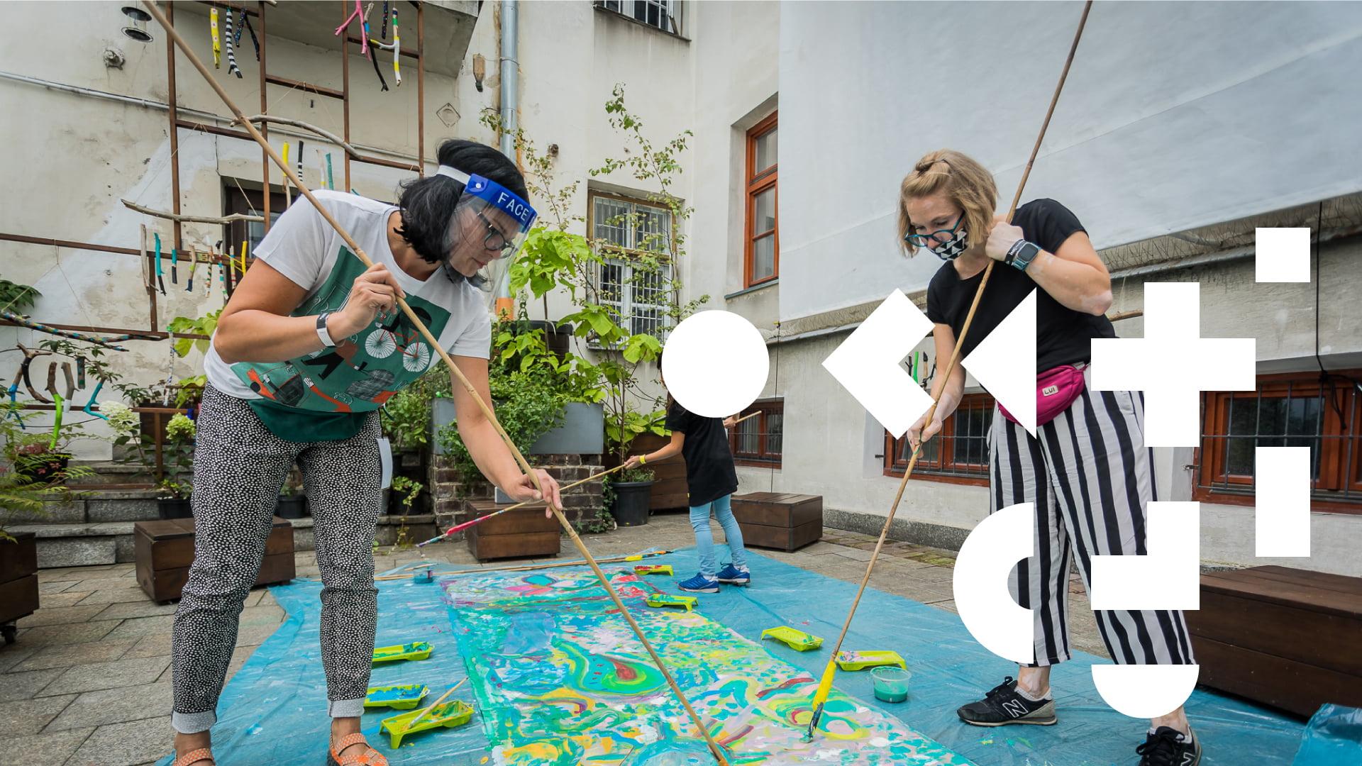 Trzy osoby malujące po materiale za pomocą pędzli na wysięgnikach. Po prawej stronie geometryczne elementy. W tle budynek oraz rośliny.