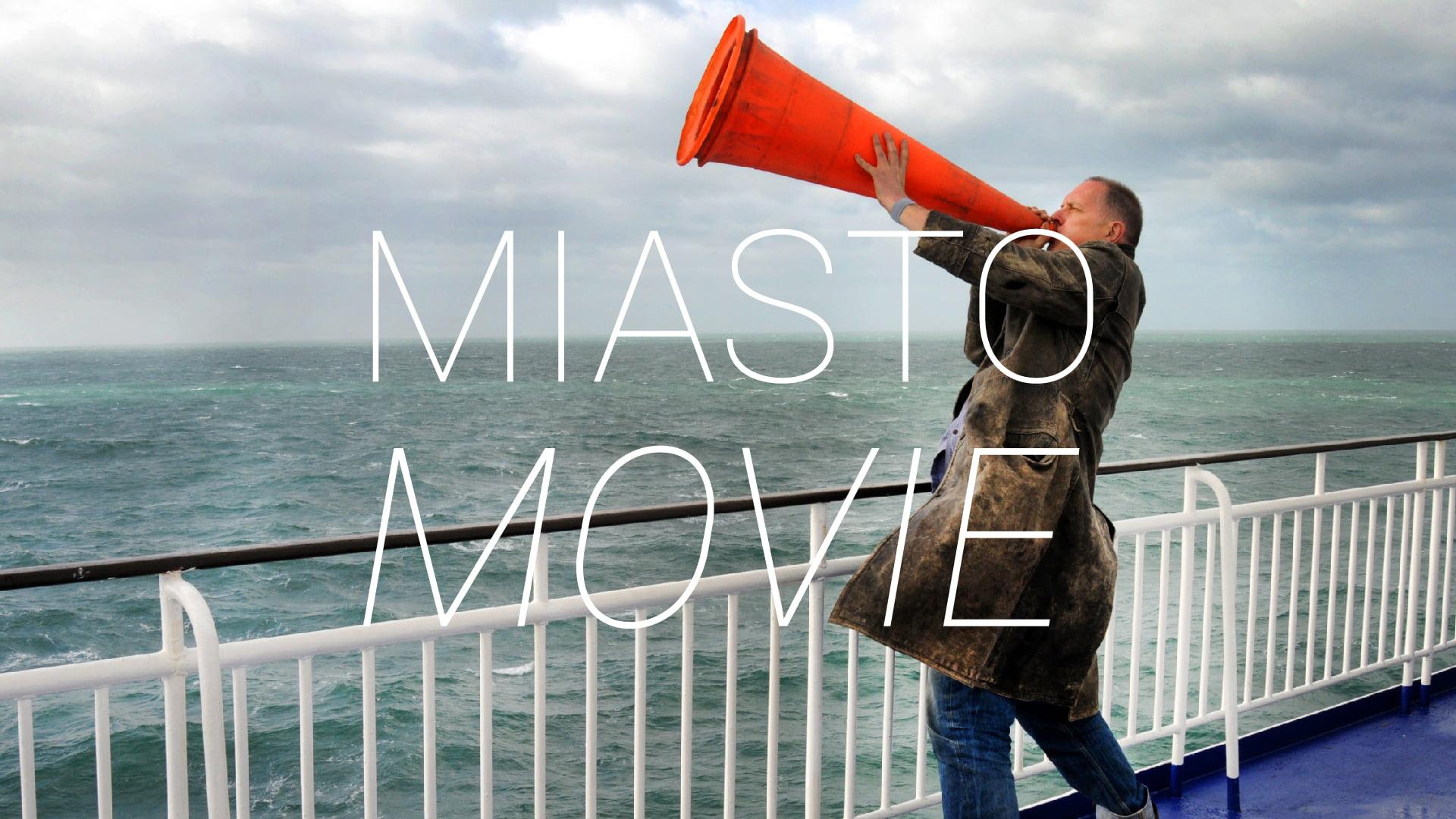 Zdjęcie mężczyzny na statku trzymający pomarańczową tubę. Napis Miasto Movie.