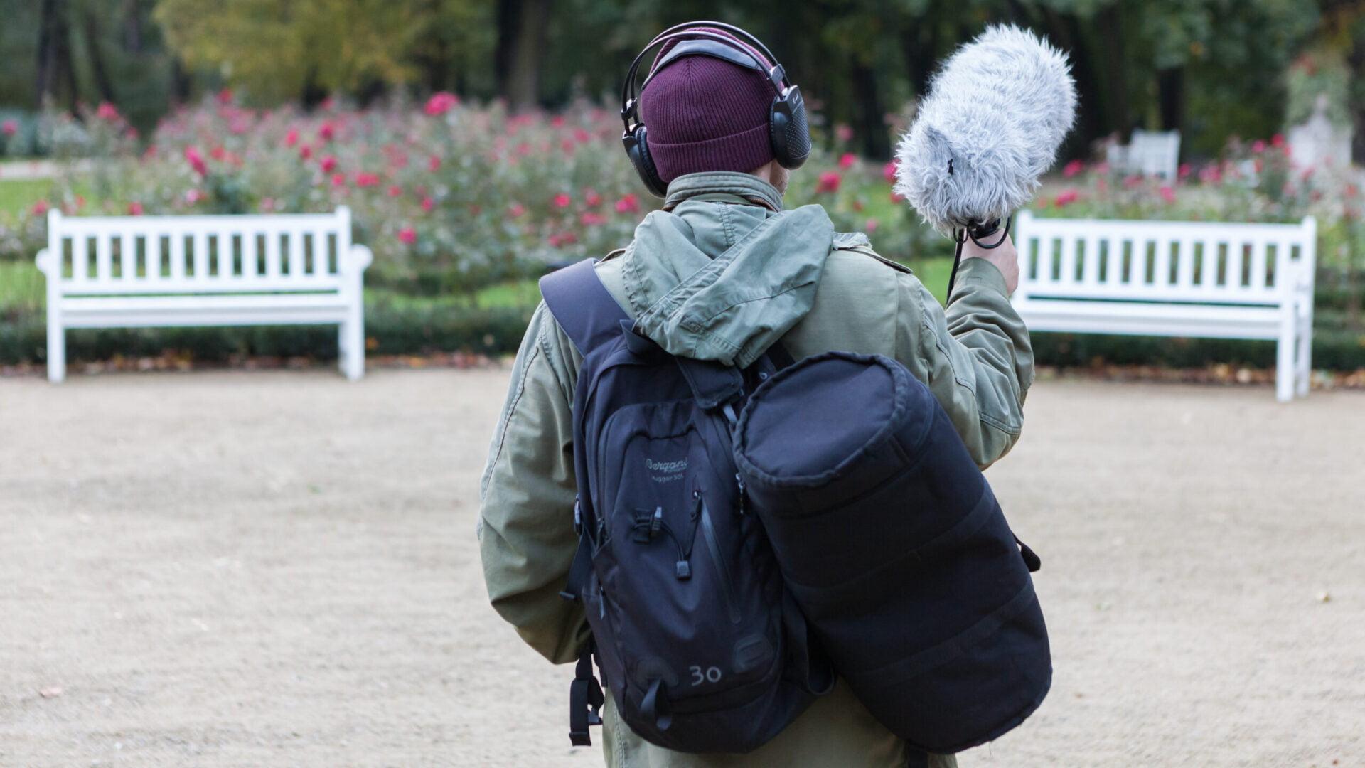 Widok z tyłu. Osoba w kurtce jesiennej, z granatowym plecakiem i torbą na sprzęt. W ręku trzyma mikrofon - futrzak. Na głowie ma czapkę i słuchawki.
