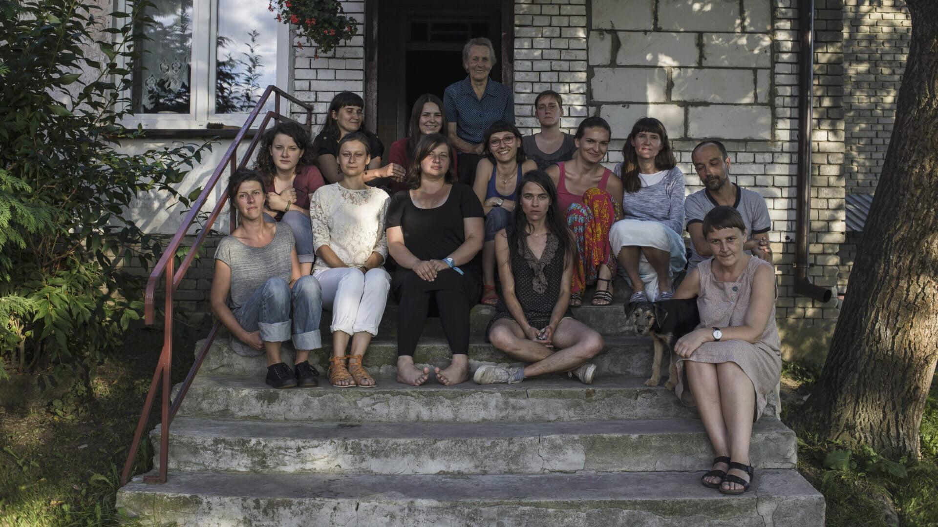 Zdjęcie grupy ludzi siedzących na schodach przed budynkiem.