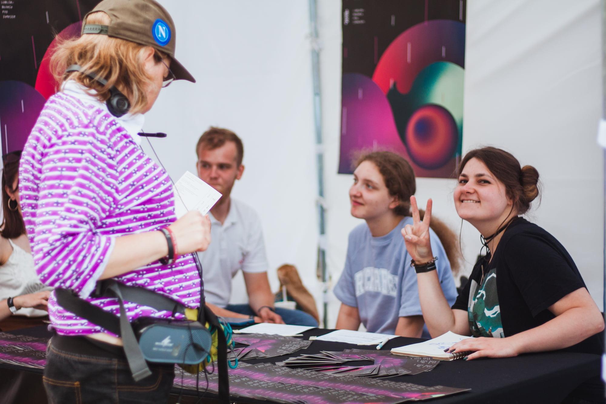 Grupa młodych ludzi przy stole z programem festiwalu oraz pani ze słuchawkami czytająca program. W tle plakat festiwalowy.
