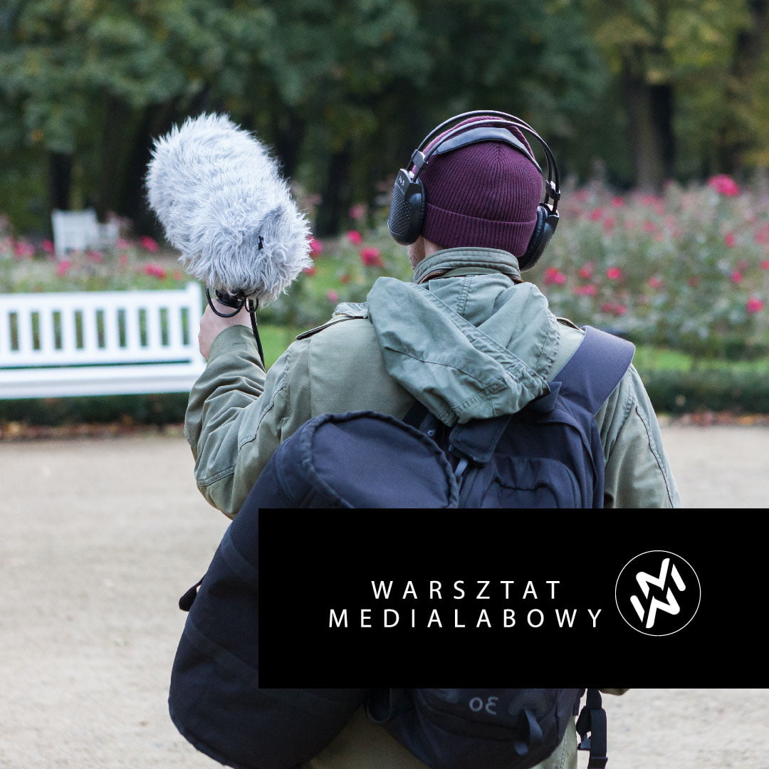 Zdjęcie mężczyzny w szaro zielonej kurtce, z czarnymi plecakami, mikrofonem, bordowej czapce oraz słuchawkach. W tle park. W dolnej części logo Warsztat Medialabowy.