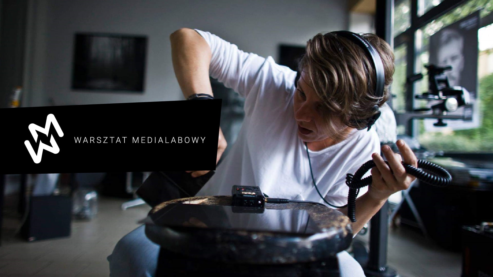 Chłopak siedzący w pokoju ze słuchawkami. W ręku trzyma kabel od słuchawek. Po lewej stronie napis Warsztat Medialabowy.