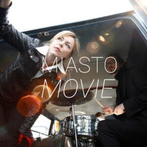 Zdjęcie kobiety i mężczyzny przy perkusji w bagażniku vana. Na środku napis Miasto Movie.