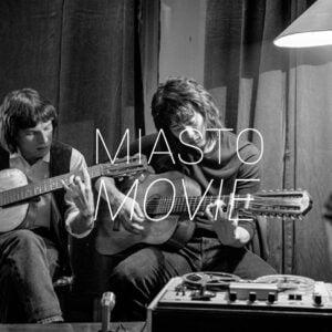Zdjęcie przedstawia dwóch mężczyzn grających na gitarach. Na środku napis Miasto Movie.