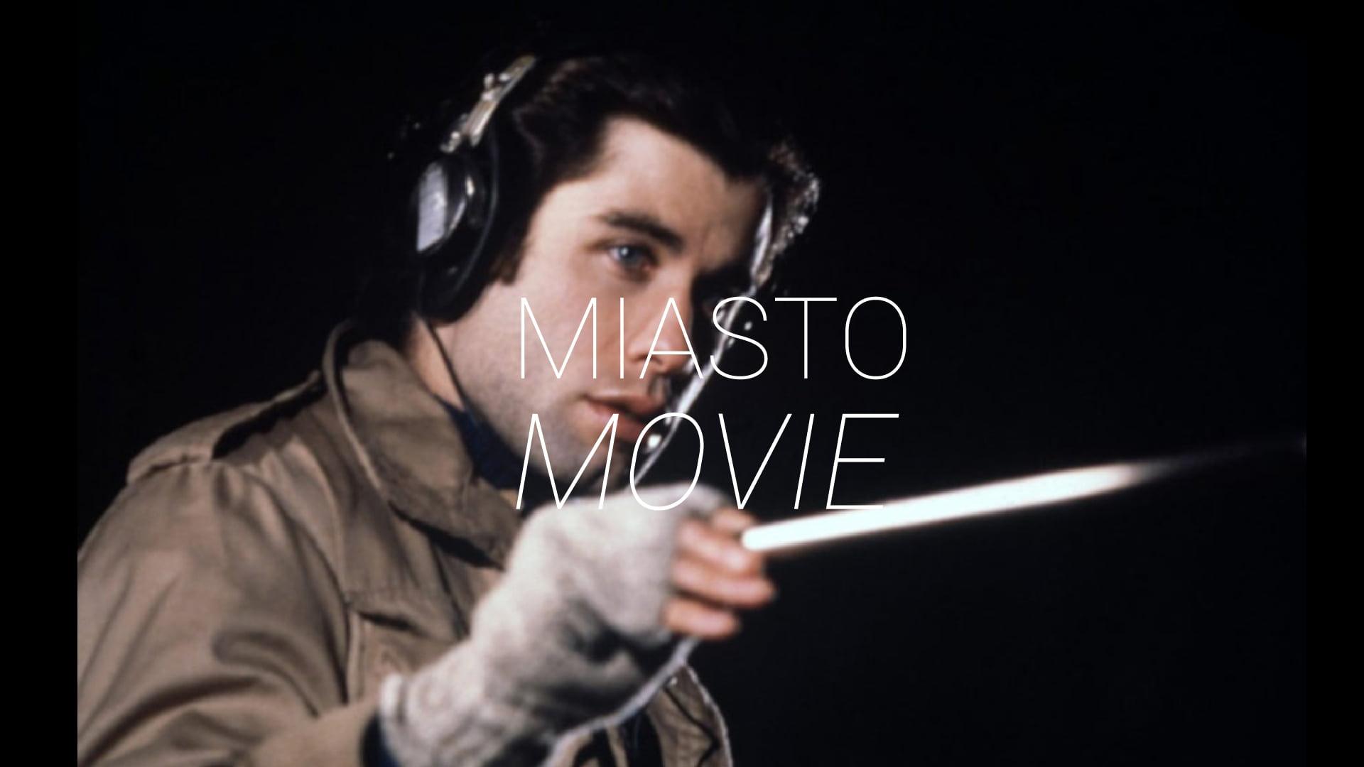 Zdjęcie mężczyzny w słuchawkach i batutą w ręku. Na środku napis Miasto Movie.