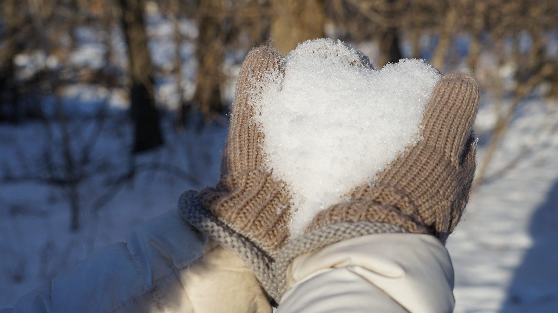 dłonie w zimowych rękawiczkach układają serce ze śniegu