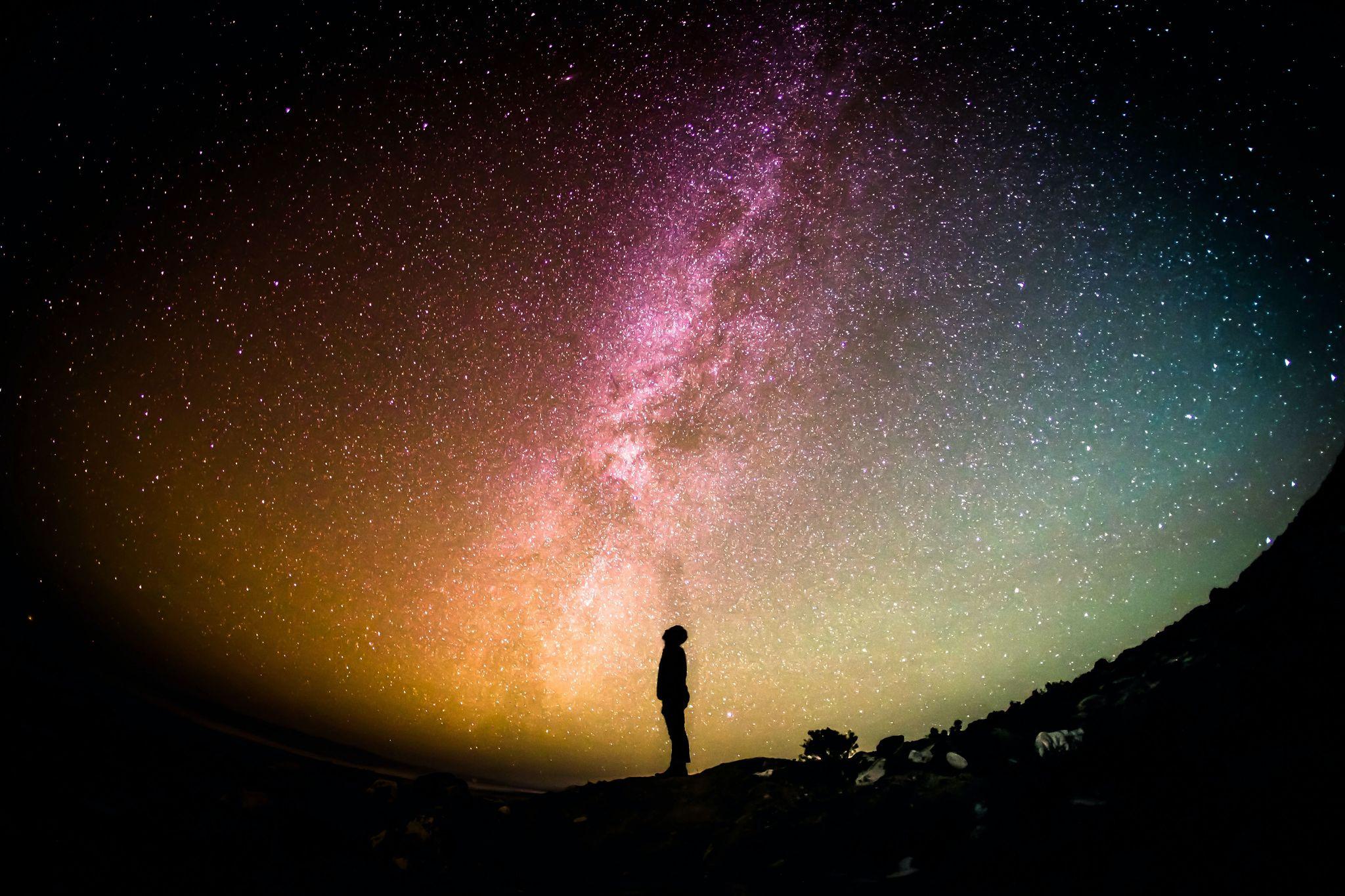 Zdjęcie osoby na tle kolorowego gwieździstego nieba.